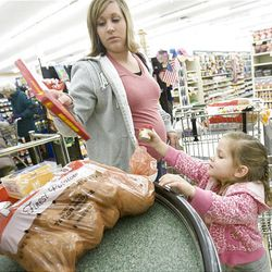 Aimee Tueller and daughter Kassidy, 3, unload their groceries at the checkout station at Bowman's grocery store in Kaysville Monday.
