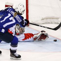 Jocelyne Lamoureux #17 of the United States scores a goal against Shannon Szabados #1 of Canada in a shootout to win.