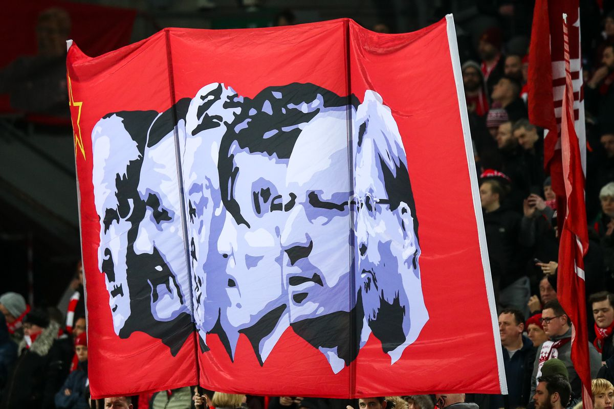 Fans at Anfield hold up a red banner featuring black and white images of past Liverpool managers, including Rafa Benítez.
