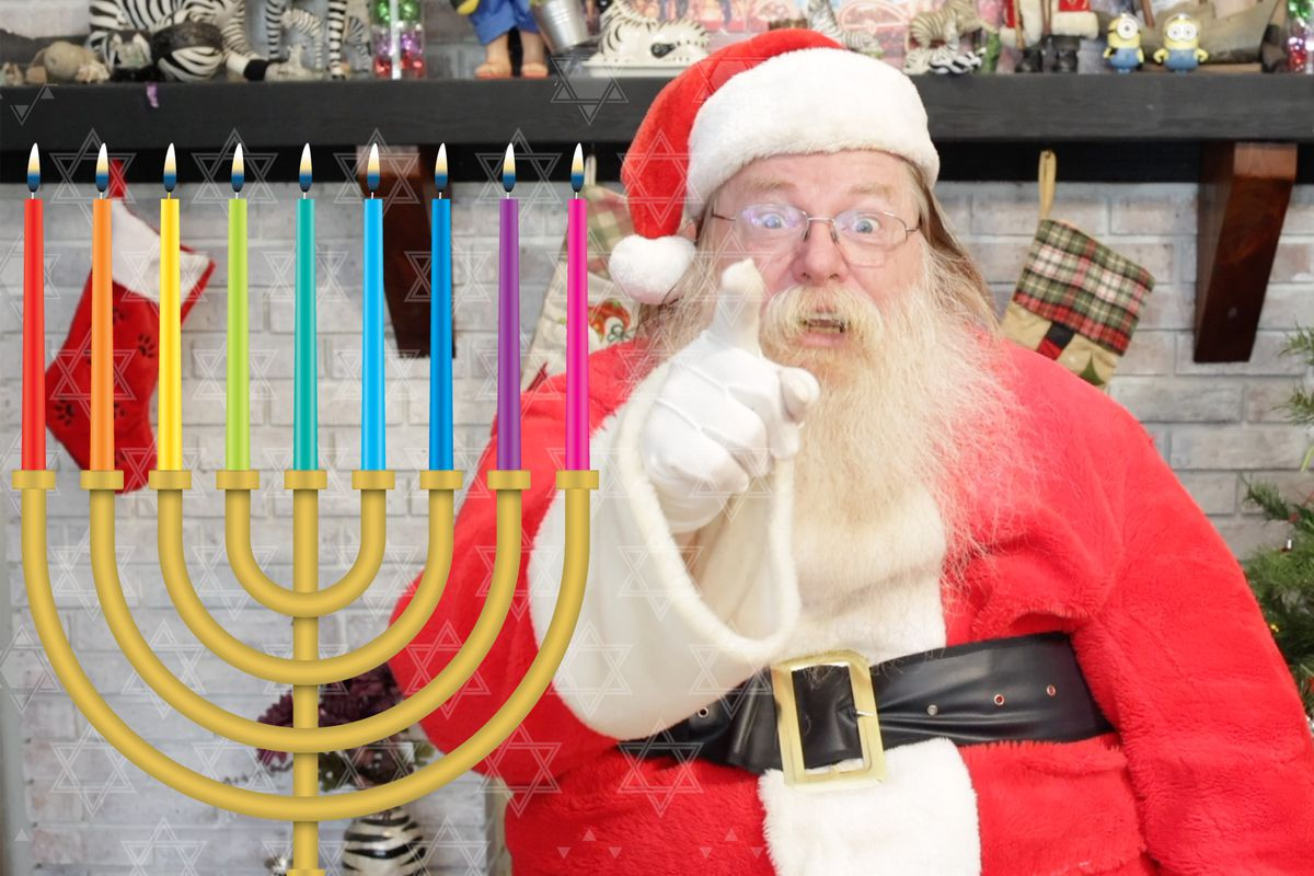 Santa Claus is pointing at you the reader next to a Hanukkiah that has all 8 candles and the shamas lit.