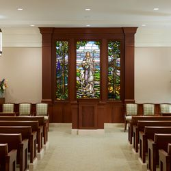The chapel in the Pocatello Idaho Temple. The image shows pews in the chapel and stained glass depicting the Savior.