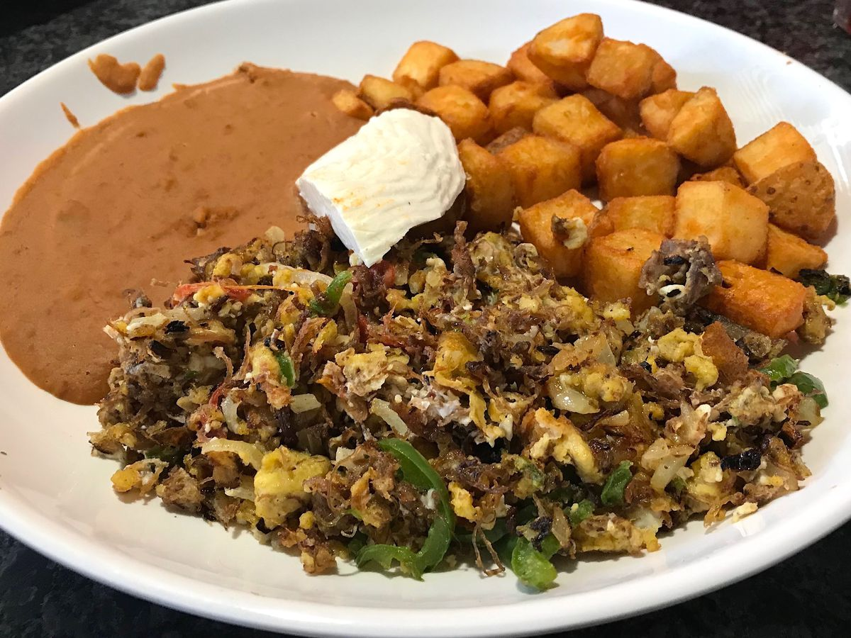 Eggs scrambled with beef on a plate with refried beans and fried potatoes