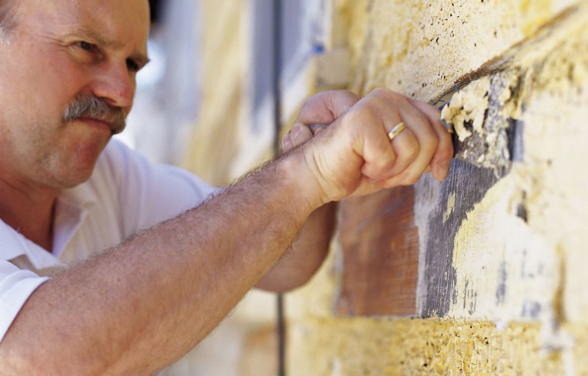 Man Removes Layers Of Exterior House Paint With Chisel