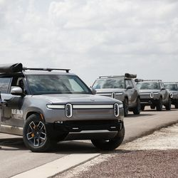 Blue Origin's fleet of Rivian electric trucks stand ready with the NS-16 crew inside before driving onto the company's New Shepard landing pad for a photo opp hours after the crew returned from space.