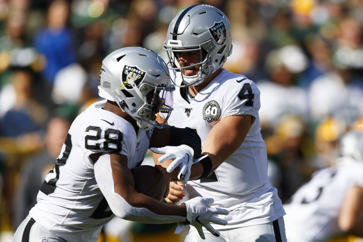 Oakland Raiders quarterback Derek Carr hands the football off to running back Josh Jacobs during the first quarter against the Green Bay Packers- at Lambeau Field.