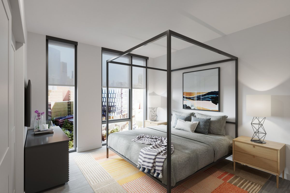 A four-post bed in a bedroom with two window overlooking the West Loop neighborhood.