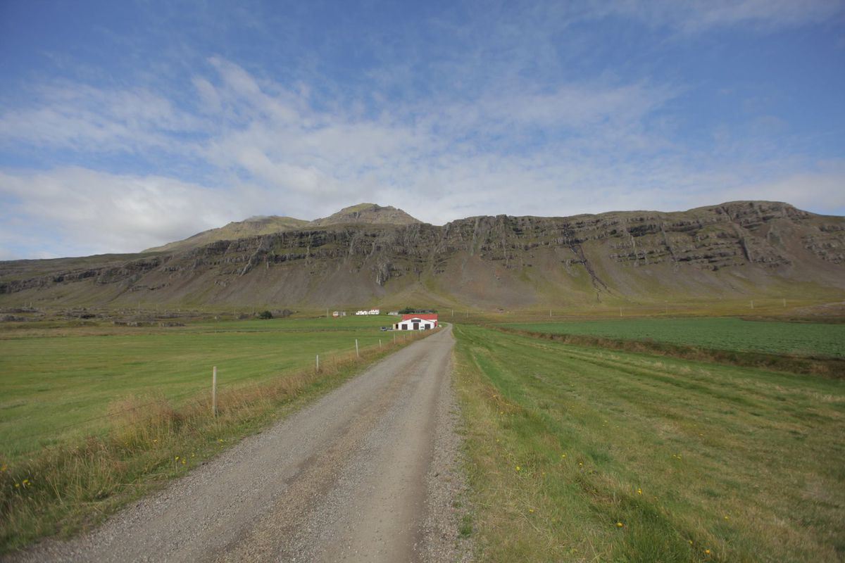 a dirt road with grass on both sides leading to a white barn with a red roof in the distance, sitting at the foot of some rocky hills