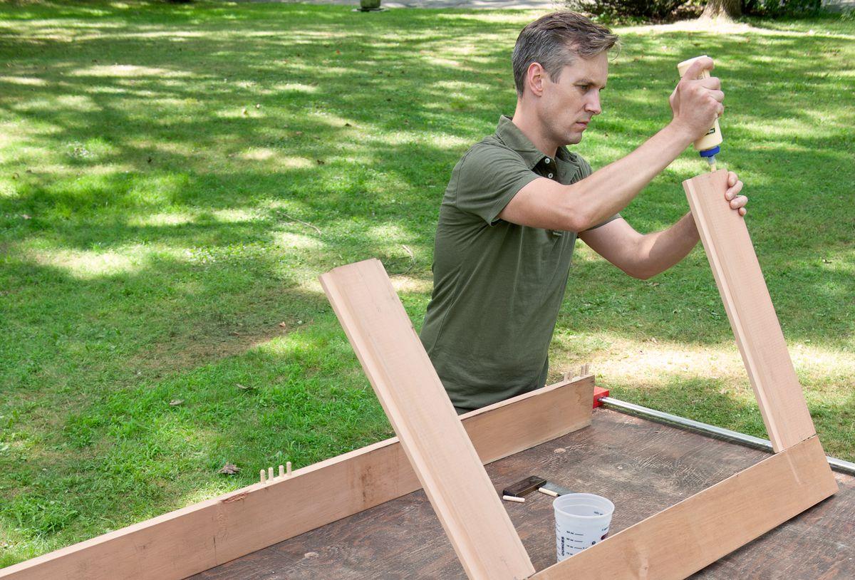Man Assembles Picnic Table Pieces