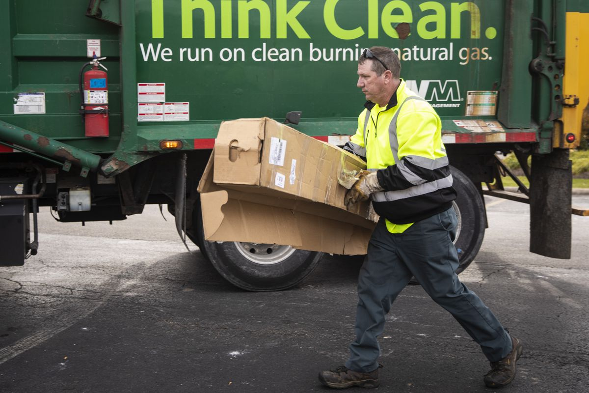 Mike Angus, a driver for Waste Management represented by the Teamsters Union, picks up a piece of garbage that was left outside of a dumpster in an apartment complex in southwest suburban Burr Ridge, Monday morning, Nov. 4, 2019.