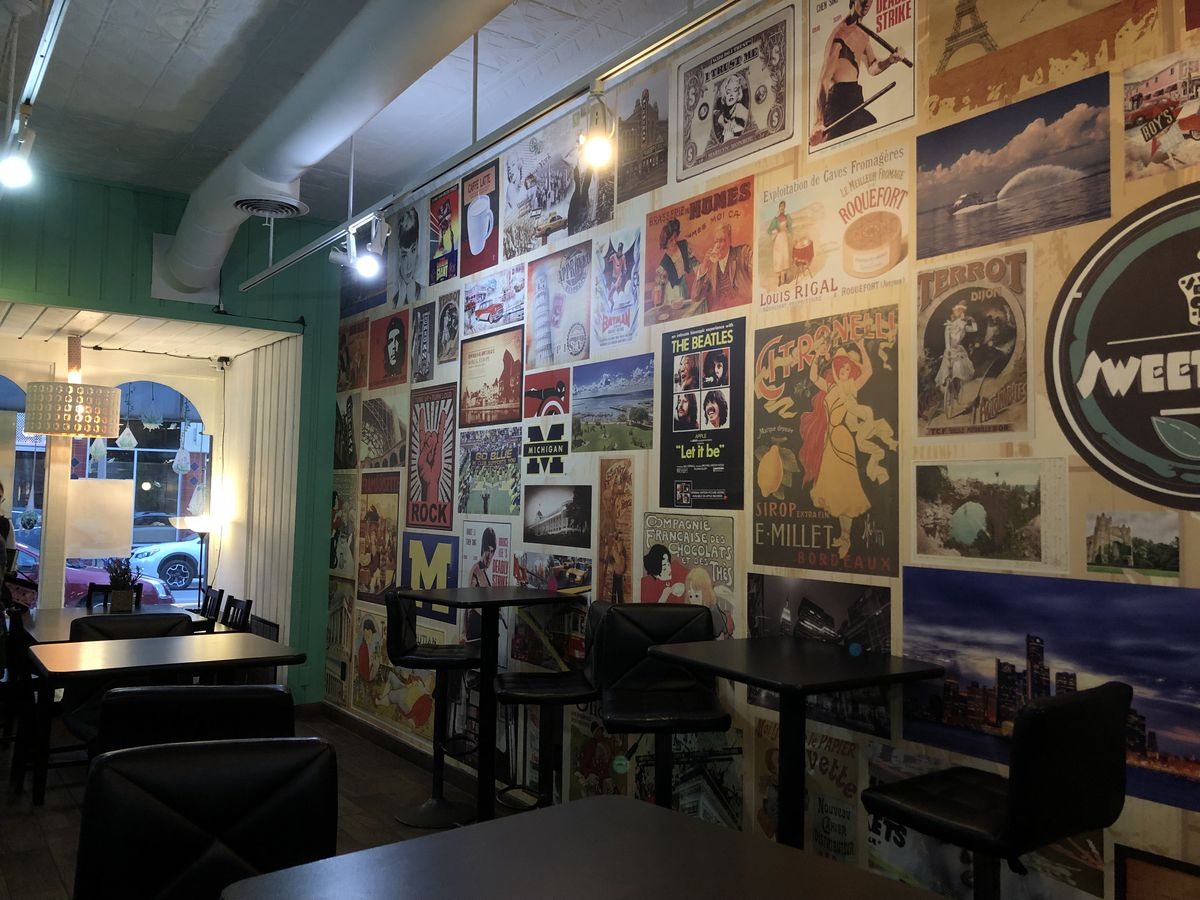 Image of Sweeting South U location. Vintage posters line a wall on the right; in the center, high-top chairs and tables are organized in two rows. The far left corner features a window onto the Ann Arbor street.