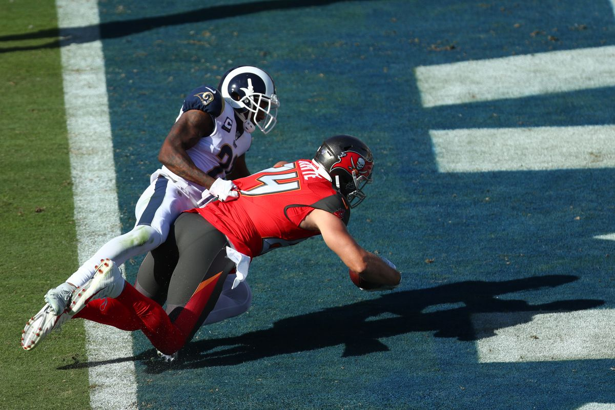 Cameron Brate of the Tampa Bay Buccaneers scores a touchdown in the fourth quarter as Taylor Rapp of the Los Angeles Rams tries to stop him at Los Angeles Memorial Coliseum on September 29, 2019 in Los Angeles, California.