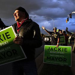 Jeremy Cunningham, front, and other supporters of Salt Lake mayoral candidate Jackie Biskupski wave to motorists in Salt Lake City on Tuesday, Nov. 3, 2015.