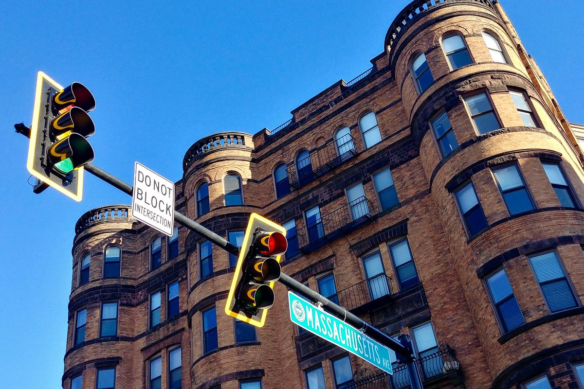 Looking up at a multistory condo building just behind a street sign and traffic light.