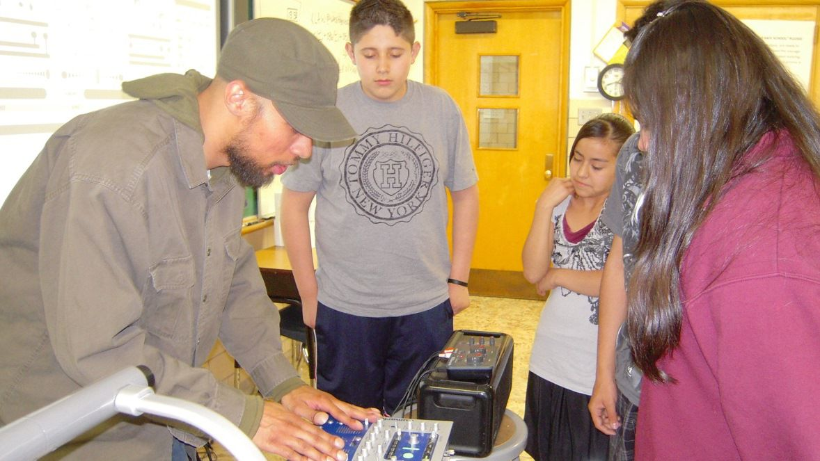 DJ Duran Cobb, left, teaches students at West Denver Prep's Harvey Park campus.
