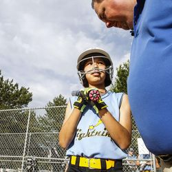 Brad Thomas, right, who has been coaching his daughter's accelerated softball team for the past five years, talks with Arianna Christensen, before she goes up to bat during a scrimmage at Dewey Bluth Park in Sandy, Utah, Thursday, June 9, 2016.