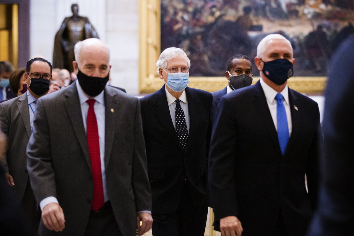 Senate Majority Leader Mitch McConnell and Vice President Mike Pence walk through the Capitol Rotunda before the building was breached by Trump supporters. Cheriss May/Getty Images