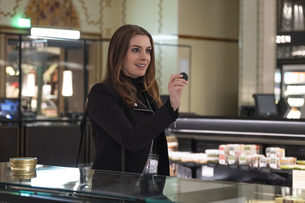 Anne Hathaway holds up a small object in Harrods in Locked Down