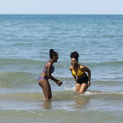 (From left) Kayla Griggs, 15, and her 14-year-old cousin Taliyah Morris, both from the West Chatham neighborhood, play in the waves of Lake Michigan at 63rd Street Beach on the South Side, Wednesday afternoon, July 24, 2019