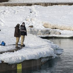 Two men fish in the mouth of Diversey Harbor, Tuesday, Feb. 23, 2021. The Chicago Parks District reopened the Lakefront Trail Tuesday.