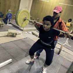 In this Monday, June 18, 2012 photo, Najwan El Zawawi, background, UAE women's weightlifter team coach, assists Khadija Mohammed, who competes in the 75-kilogram category and will be the first female lifter from the Gulf at the Olympics and the first Emirati to qualify for the Olympics outright, at the Al Shabab stadium in Dubai, United Arab Emirates.