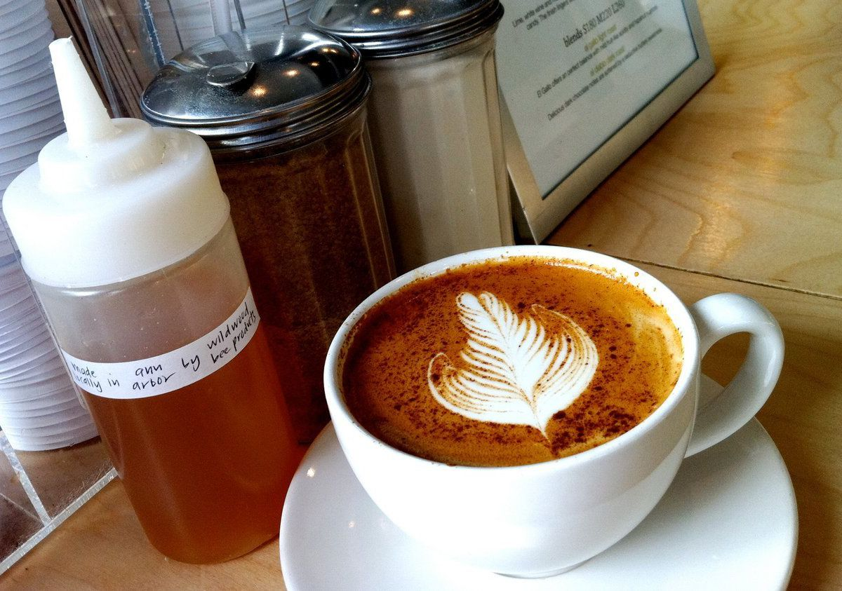 A latte in a white teacup next to a honey squeeze bottle.