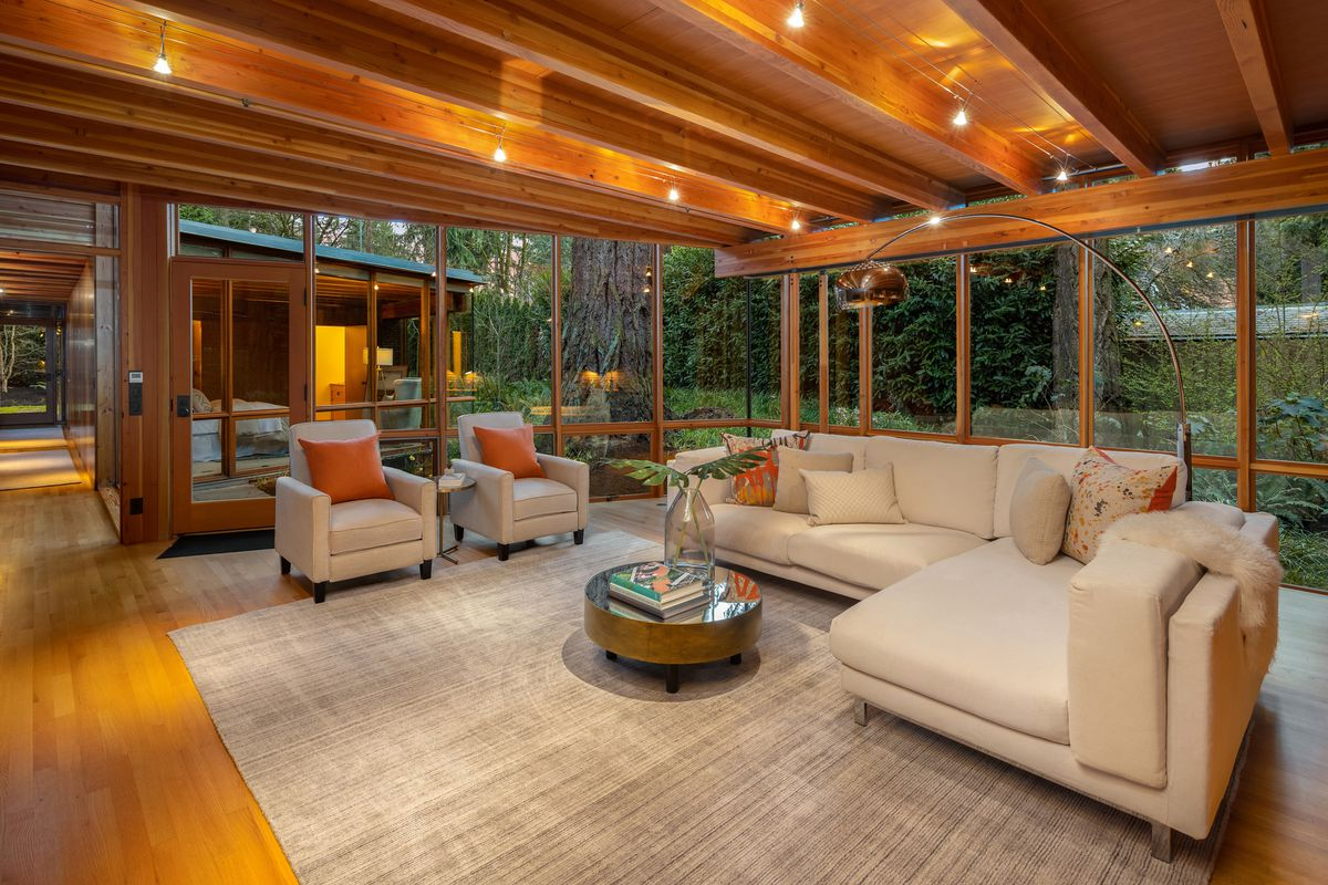 A family room has timber ceilings, glass walls, and white couches.