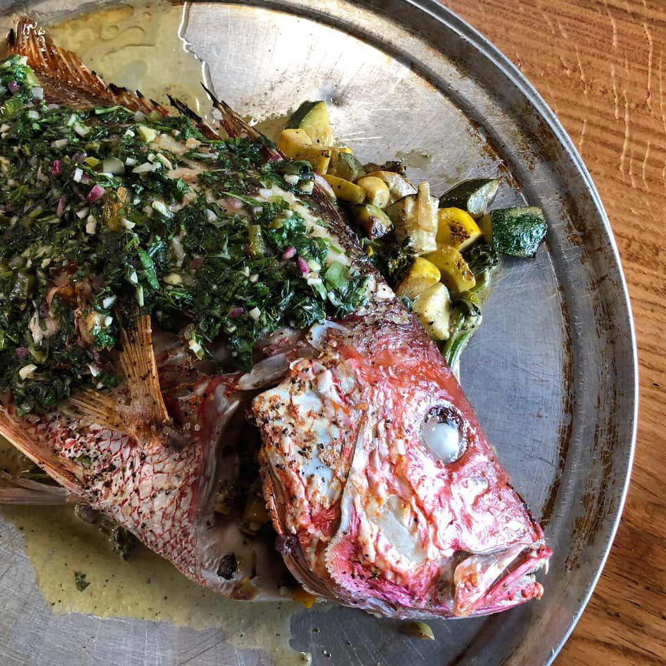 A roasted whole fish on a silver platter dressed with herbs and a side of roasted squash