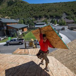 Martin Fragoso Villegas works on building a zero energy ready home in the Treseder at Little Cottonwood development in Sandy on Friday, Aug. 12, 2016. The development's model home, pictured in background, is featured in the Parade of Homes.