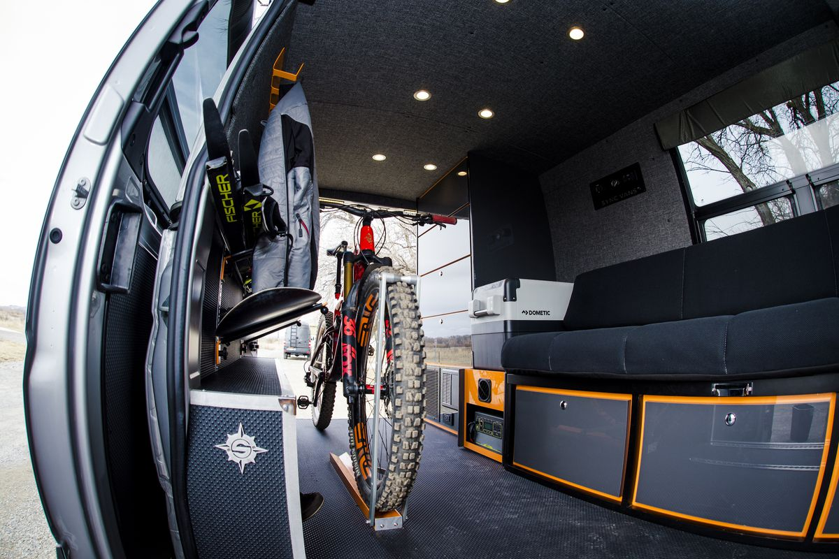 The interior of a camper van. There is a bicycle, a seat, and storage compartments.