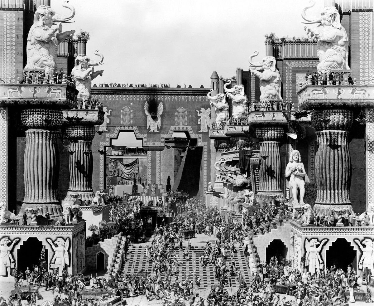"""A still from the 1916 film """"Intolerance"""" featuring decadent Babylonian architecture including columns topped with elephants and hundreds of actors."""