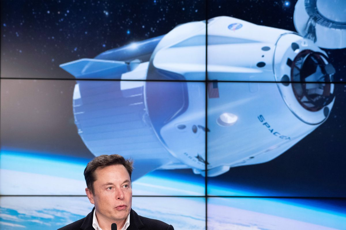 SpaceX chief Elon Musk onstage in front of a picture of a manned space capsule.