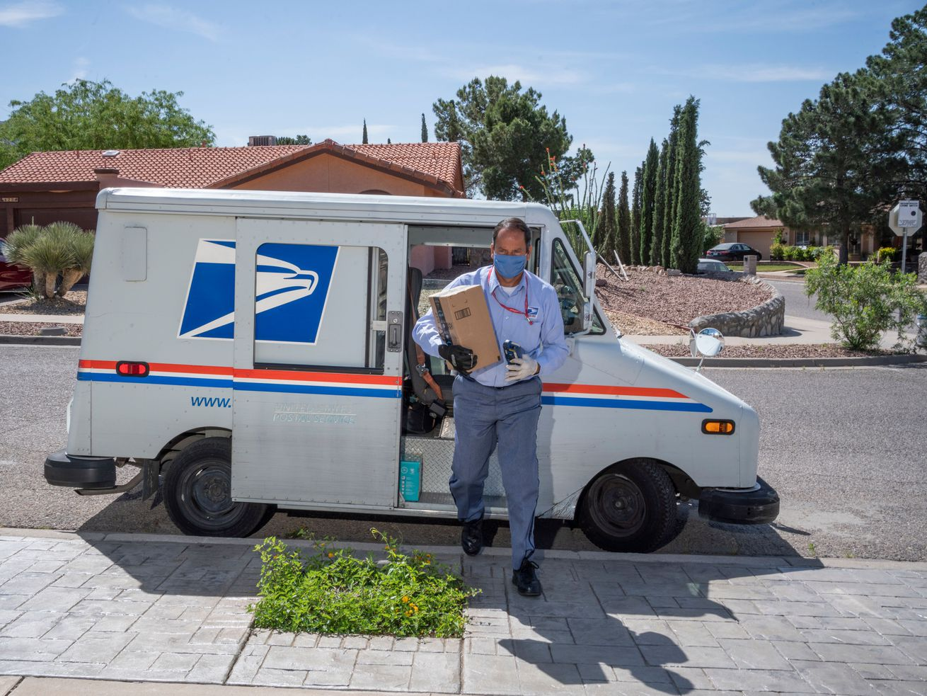 A postal employee carrying a package from their van.