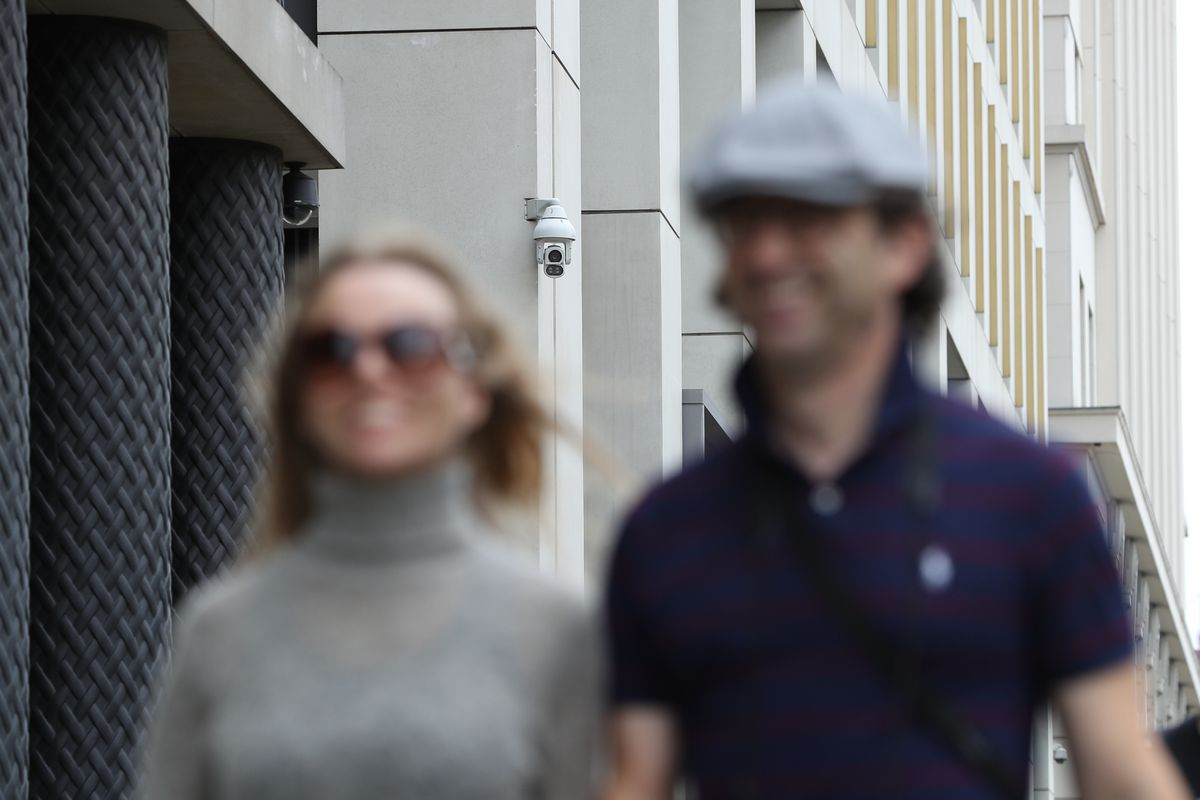 A man and a woman in the foreground are blurry, while a surveillance camera watching from behind them is in focus.