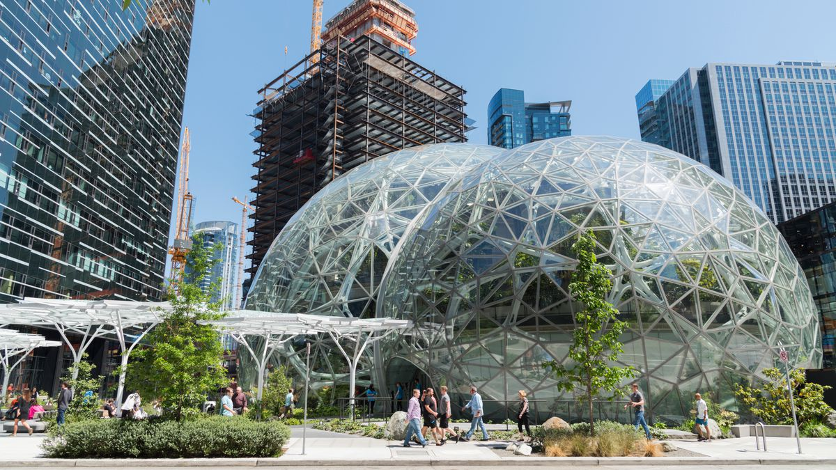 Two giant glass domes filled with plants sit in the courtyard of an urban plaza with dozens of high-rise buildings in the background, one with a bright yellow crane.