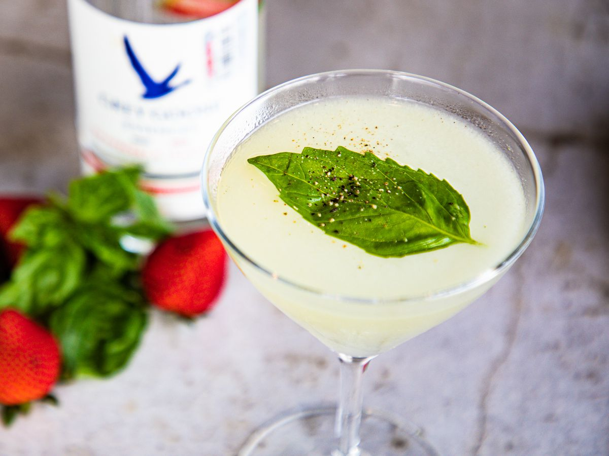 The Grey Goose Le Poir cocktail in a martini glass and topped with herbs on a marble counter at Toulouse. Also on the counter are strawberries, herbs, a pepper grinder and a Grey Goose bottle.