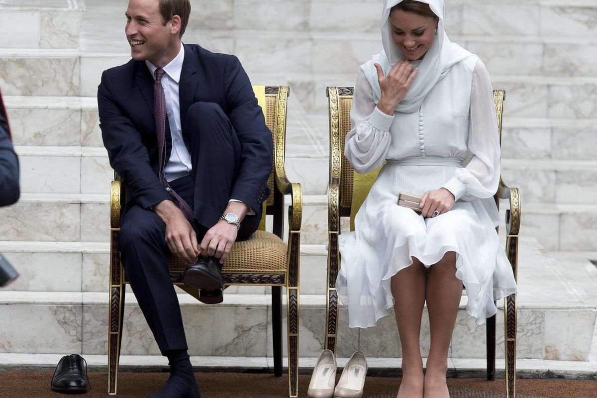 Prince William and his wife Kate, the Duke and Duchess of Cambridge take their shoes off before entering a mosque in Kuala Lumpur, Malaysia, Friday, Sept. 14, 2012.