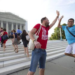 Gay rights activist Bryce Romero, who works for the Human Rights Campaign, offers an enthusiastic high-five to visitors getting in line to enter the Supreme Court on a day when justices are expected to hand down major rulings on two gay marriage cases that could impact same-sex couples across the country, in Washington, Wednesday, June 26, 2013.