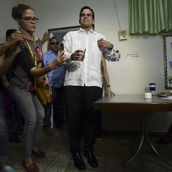 Gov. Ricardo Rossello goes through registration before voting at the San Jose Academy during the fifth referendum in San Juan, Puerto Rico, Sunday, Jun. 11, 2017. Puerto Ricans are getting the chance to tell U.S. Congress on Sunday which political status they believe best benefits the U.S. territory as it remains mired in a deep economic crisis that has triggered an exodus of islanders to the U.S mainland. Congress ultimately has to approve the outcome of Sunday's referendum that offers voters three choices: statehood, free association/independence or current territorial status.