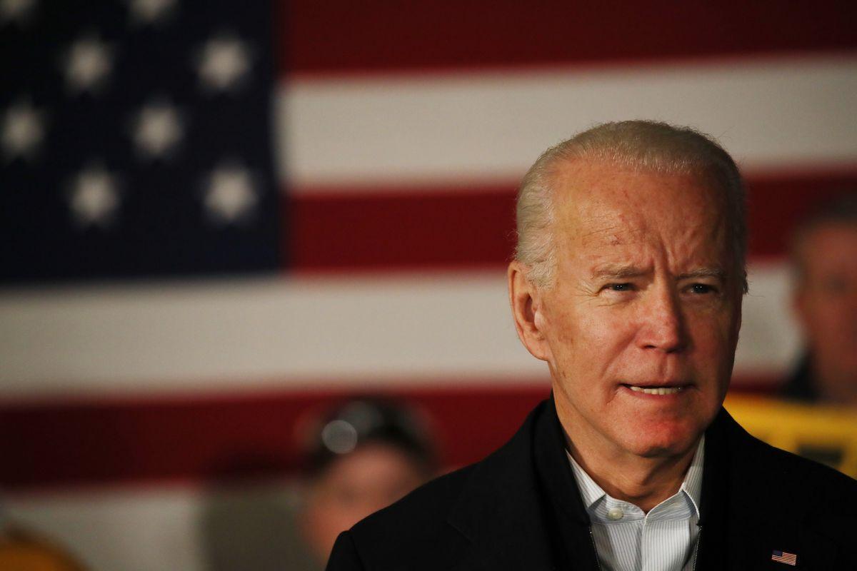Biden speaks solemnly in front of a US flag.