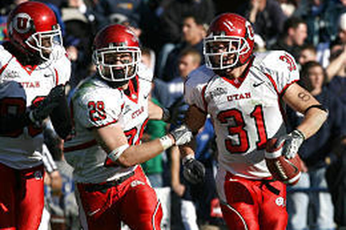 Utah's Casey Evans, right, celebrates with Steve Tate (28) after ripping ball out of Cougar running back Fahu Tahi's hands for the game's only turnover Saturday.