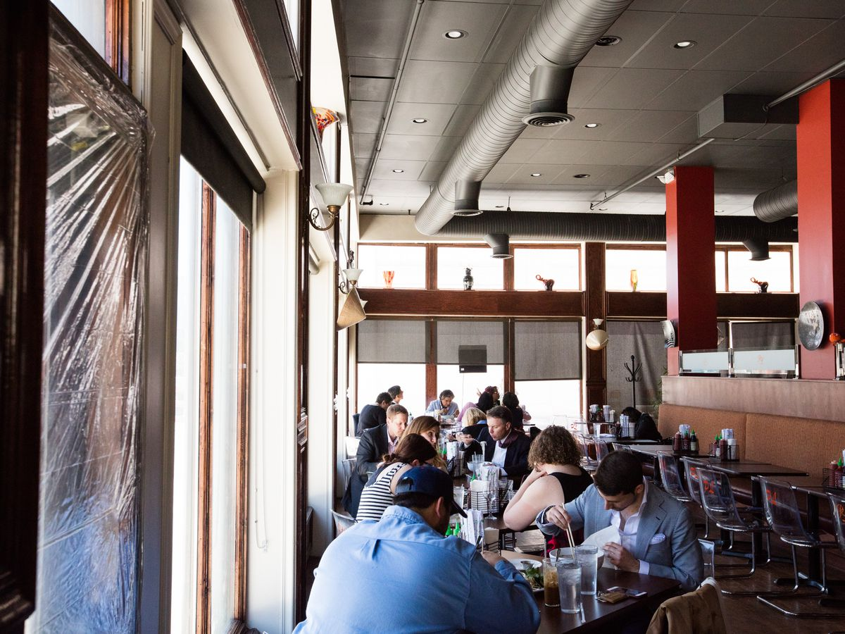 Customers dine at tables next to the Woodward facing windows at Pho Lucky
