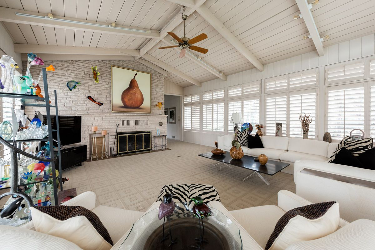 A white huge family room with a white couch and white carpet.