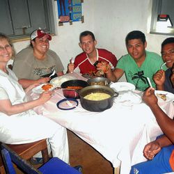 Nurses Cheryl Wynkoop and Whitney Davidson, along with their four missionary translators, eat a dinner prepared for them by Vanuatu locals.
