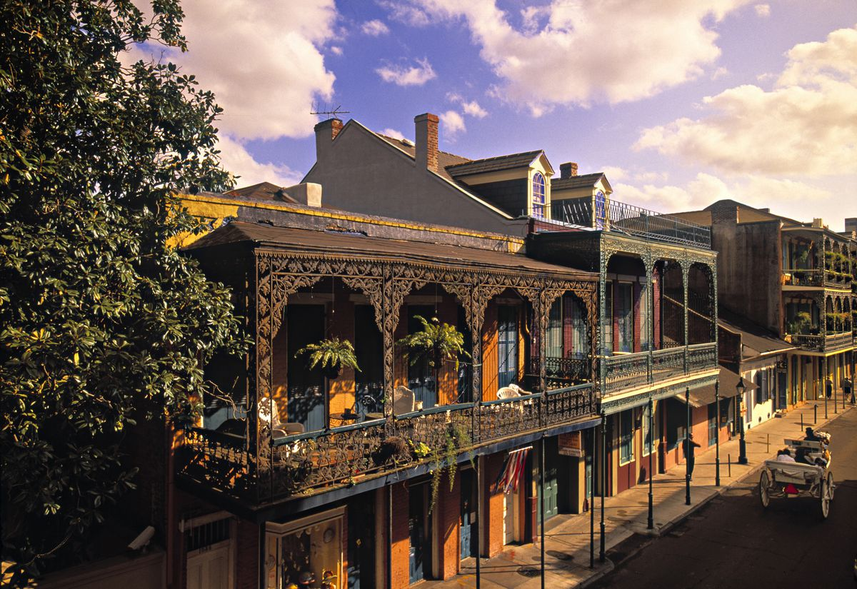 Royal Street in New Orleans. There are iron balconies on the facades of the colorful buildings that line the block.