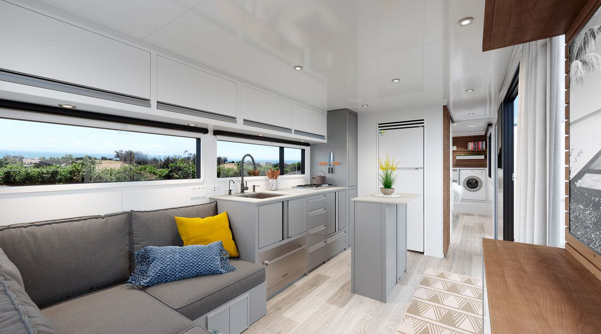 A look into the kitchen area, with lounge seating on the left and a kitchen with gray cabinets, white countertops, an island, and large windows.