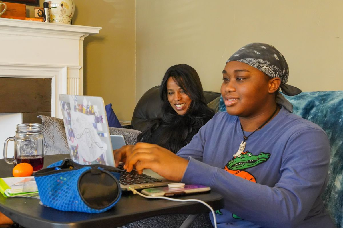 Kim Tyler, left, and her daughter Madison spend an April morning completing remote learning lessons from the couch at their South Side home.