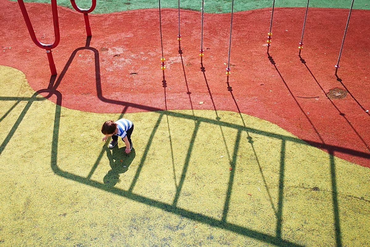 A boy plays in the shadows of playground equipment on a yellow and red ground surface.