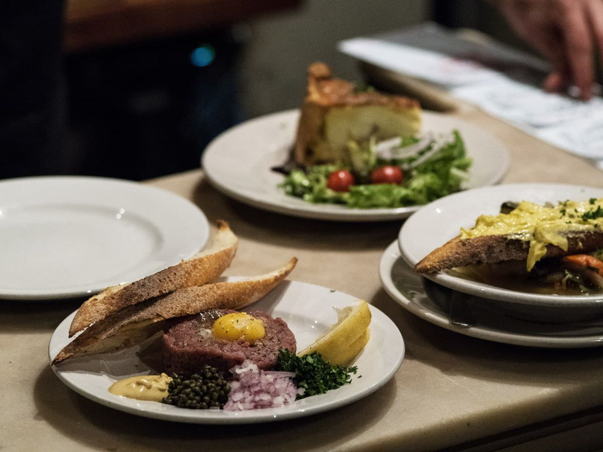 A countertop with a plate of egg-topped beef tartare, toast with thick yellow topping, and quiche with salad