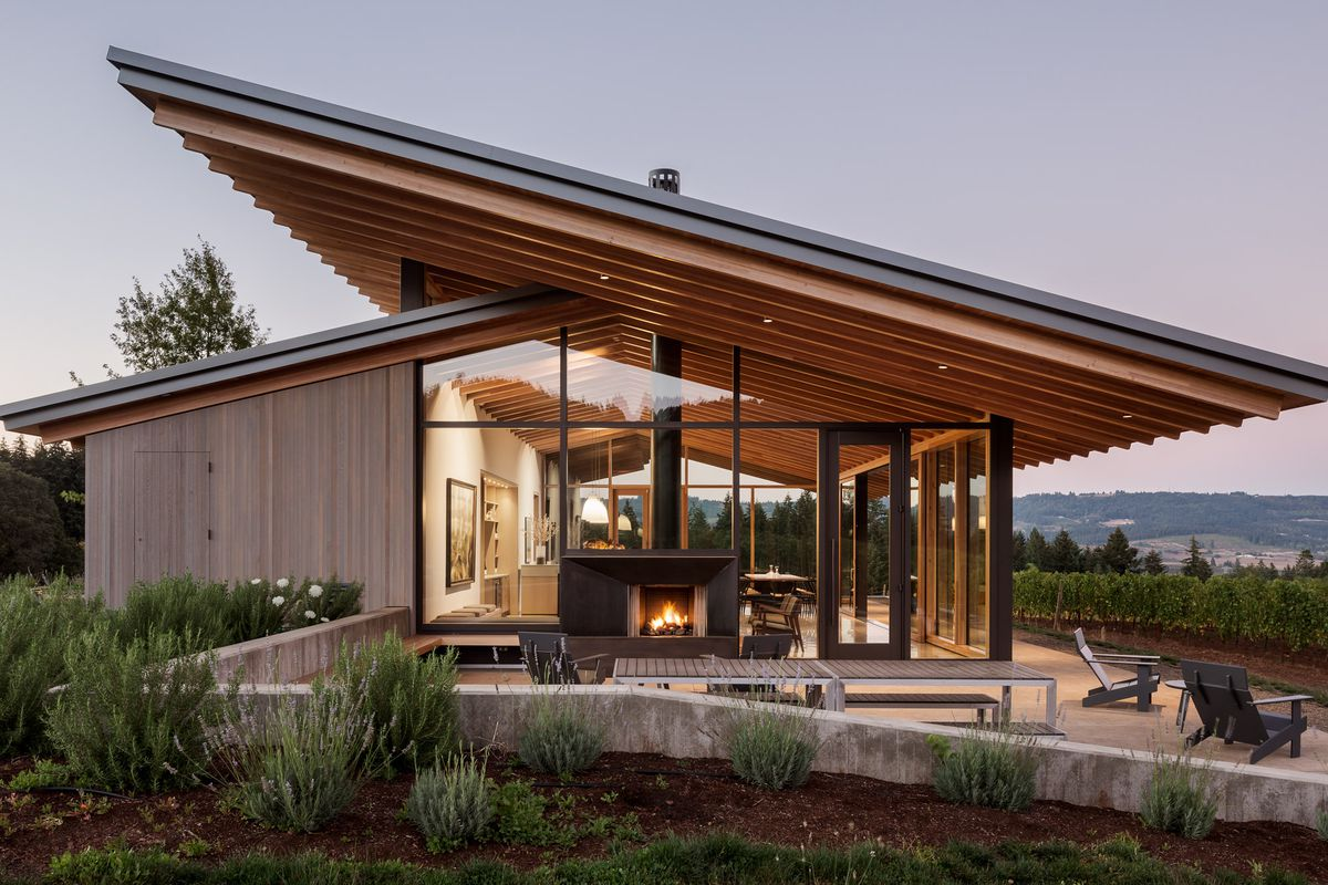 Side profile of a simple structure with one large plane forming the roof on one side that overhangs at both ends, walls of glass, and a terrace with outdoor fireplace set amid a lush vineyard.