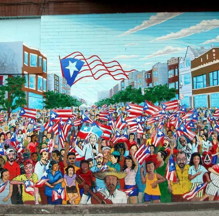 """Gamaliel Ramirez's """"Sea of Flags"""" mural at Division and Campbell. He worked himself into the mural in the bottom right quadrant, wearing glasses, head tilted and holding a painter's palette. 